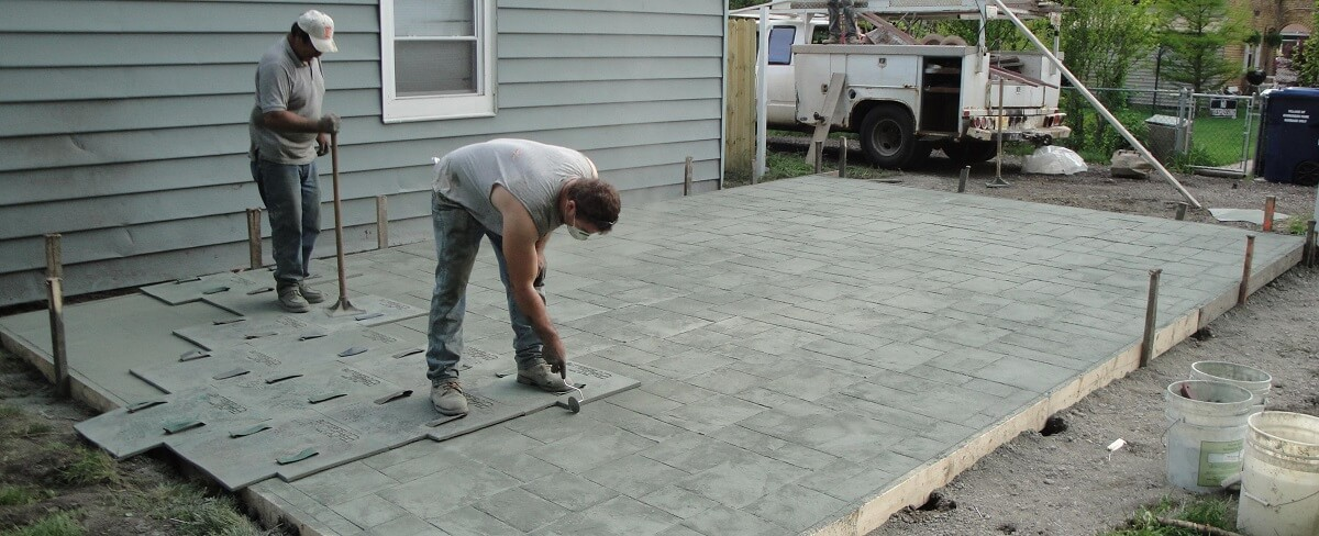 workers making a stamped concrete patio